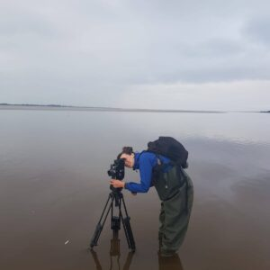 Julia Parks with her Bolex 16mm camera in the Solway Firth. Image by Heather Andrews.